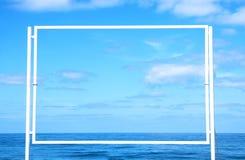 空的白色广告牌的图象在蓝色海和天空海滩infront的  对大模型和广告 库存图片