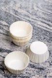 空的白色杯子蛋糕装入在灰色花岗岩大理石背景的容器 免版税图库摄影