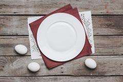 空的白色板材和在木桌上的复活节彩蛋顶视图在餐巾的 库存图片