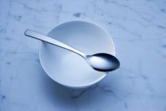 空的碗和匙子背景 免版税库存照片