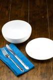 空的碗和盘与叉子,刀子,蓝色家庭用亚麻布 免版税库存照片