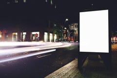 空的社会信息委员会在有汽车的运动的夜城市在背景的,给横幅的嘲笑做广告在路旁 库存照片
