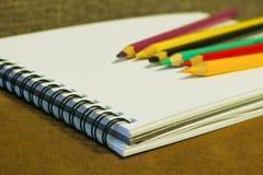 空的笔记本和五颜六色的铅笔在棕色背景 库存图片