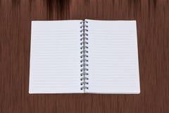空的笔记本有棕色木背景 免版税库存图片