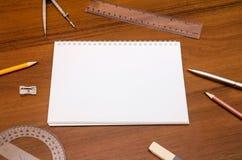 空的笔记薄,笔,铅笔在黑暗的木背景的统治者指南针 免版税库存图片
