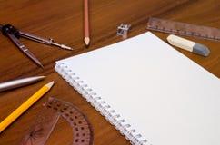 空的笔记薄,笔,铅笔,统治者,在黑暗的木背景的指南针 免版税库存图片