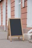 空的粉笔板在街道上站立 有一个地方为 库存照片