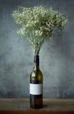 空的红葡萄酒玻璃瓶和花 免版税库存照片