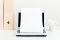 空的纸片当在膝上型计算机前面的拷贝空间在白色w 免版税库存图片