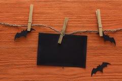 空的纸牌在与装饰棒的晒衣夹垂悬在橙色木背景 背景棒万圣节月光附注 免版税图库摄影