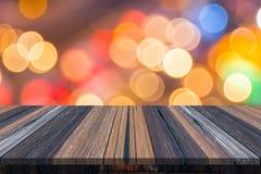 空的老被绘的颜色木桌或板条与光bokeh从路或街道有城市塔的在背景 库存照片