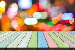 空的老被绘的颜色木桌或板条与光bokeh从路或街道有城市塔的在背景 库存图片