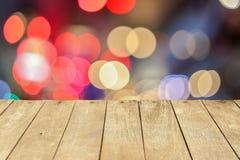 空的老被绘的颜色木桌或板条与光bokeh从路或街道有城市塔的在背景 免版税库存图片