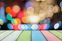 空的老被绘的颜色木桌或板条与光bokeh从路或街道有城市塔的在背景 免版税库存照片