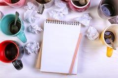 空的肮脏的咖啡杯、不同颜色在桌上和一个笔记本写的信 概念咖啡因麻醉药,缺乏能量 库存图片
