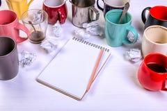 空的肮脏的咖啡杯、不同颜色在桌上和一个笔记本写的信 概念咖啡因麻醉药,缺乏能量 图库摄影