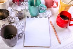 空的肮脏的咖啡杯、不同颜色在桌上和一个笔记本写的信 概念咖啡因麻醉药,缺乏能量 免版税库存图片