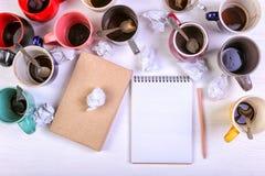 空的肮脏的咖啡杯、不同颜色在桌上和一个笔记本写的信 概念咖啡因麻醉药,缺乏能量 免版税图库摄影