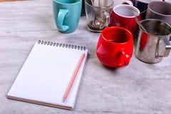 空的肮脏的咖啡杯、不同颜色在桌上和一个笔记本写的信 概念咖啡因麻醉药,缺乏能量 免版税库存照片