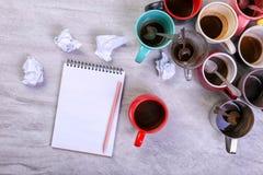 空的肮脏的咖啡杯、不同颜色在桌上和一个笔记本写的信 概念咖啡因麻醉药,缺乏能量 库存照片