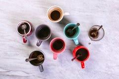 空的肮脏的咖啡杯在桌上的不同颜色 咖啡因麻醉药的概念,缺乏能量和长的等待 复制空间 免版税图库摄影