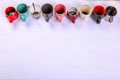 空的肮脏的咖啡杯在桌上的不同颜色 咖啡因麻醉药的概念,缺乏能量和长的等待 复制空间 免版税库存照片