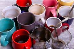 空的肮脏的咖啡杯在桌上的不同颜色 咖啡因麻醉药的概念,缺乏能量和长的等待 复制空间 库存图片