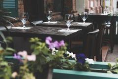 空的葡萄酒杯在外面桌上的餐馆 装饰开花背景 库存图片