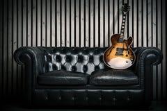 空的葡萄酒沙发和电吉他有现代木墙壁录音室背景 与没人的音乐概念 库存照片