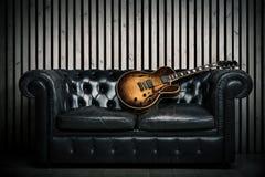 空的葡萄酒沙发和电吉他有现代木墙壁录音室背景 与没人的音乐概念 库存图片