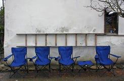 空的蓝色可折叠轻便折椅和桌在有一架梯子的土气白色墙壁前面排队了在墙壁上 图库摄影