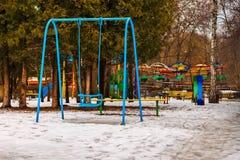 空的蓝色摇摆和儿童操场在冬天停放,户外 免版税库存图片