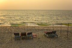 空的蓝色海滩床在黄沙的绿色黄色机盖下反对平衡的日落的海 免版税库存图片