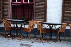 空的街道咖啡馆在欧洲老镇 空的桌和椅子反对老白色砖瓦房与开放快门和红色窗口 库存照片