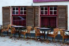 空的街道咖啡馆在欧洲老镇 空的桌和椅子反对老白色砖瓦房与开放快门和红色窗口 免版税库存照片