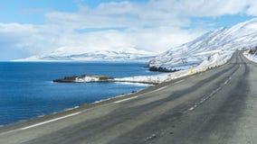 空的路标题到与一个湖的多雪的山里在一边 免版税库存图片