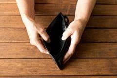 空的钱包在一个年长人的手上在一张木桌上的 T 库存图片