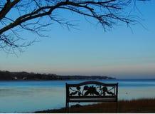 空的长凳剪影由水的 图库摄影