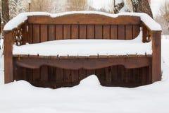 空的长木凳在积雪的公园 背景蓝色雪花白色冬天 户外 库存照片