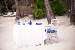空的露天桌为在白色海滩的晚餐设置了 免版税库存图片