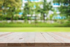 空的顶面木桌和晴朗的摘要弄脏了bokeh backgrou 免版税库存照片