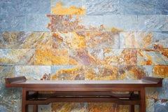 空的顶面木桌和自然石墙背景 免版税库存照片