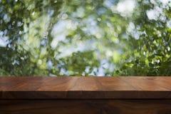 空的顶面木桌和花卉被弄脏的背景 免版税库存照片