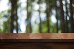 空的顶面木桌和花卉被弄脏的背景 免版税图库摄影