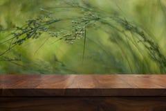空的顶面木桌和花卉被弄脏的背景 库存照片