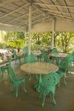 空的餐馆在绿色棕榈树与大理石桌和绿色wrought-iron椅子中的一个白色机盖下 免版税库存图片