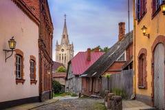 空的鹅卵石街道和高耸在小镇Cesis 免版税库存照片