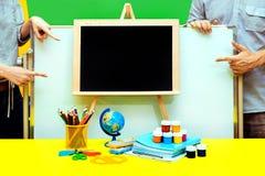 空的黑板手学校笔记本板男女油漆地球铅笔表四显示黄色蓝色 免版税库存照片