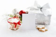 空的贺卡和圣诞节礼物盒在银色包装纸在白色蓬松背景 充分瓶子星曲奇饼 C 库存图片