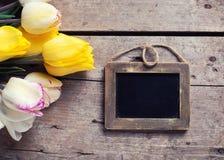 空的黑板和黄色和白色春天郁金香 免版税库存图片